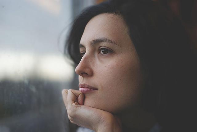 Frau am Fenster denkt an Neuanfang nach Trennung